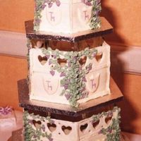 Wedding Folly 3 tier wedding cake, chocolate fudge sponge inside with ivory fondant icing cover. Royal icing runout panels and shields. All trailing...