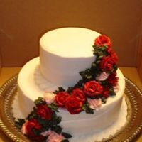 Pink And Red Roses round wedding cake with red and pink buttercream roses and deep green leafs