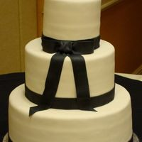 Black And Ivory Simply Bows Wedding Cake 6, 10, 14 in rounds, 4 layers, white cake w/ raspberry and lemon. sugarshack buttercream, satin ice fondant, fondant embossed ribbon border...