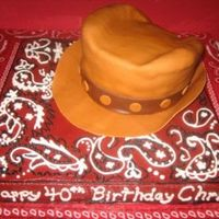 Cowboy Hat And Bandana Cake 12 inch square cake for the base covered with chocolate buttercream with red coloring added to make frosting dark red. Hat covered with MMF...