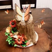 Tree Stump Cake With Gumpaste Flowers Tree stump cake with hand made gumpaste flowers. Large butterfly pastilliage. Smaller ones gumpaste. A few feather butterflies added.