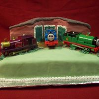 Thomas Train Yard The cake is covered in fondant. The train cars are toys my neighbor had; the cake was for her son.