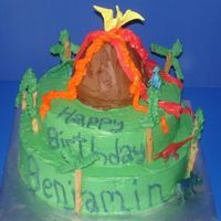 Volcano And Dinosaur Cake Cake I made for a neighbor. It is a 2 tier cake with a volcano made with a giant cake ball. Trees are royal icing and pretzel sticks.