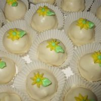 Cake Balls/truffles Lemon cake and lemon icing inside. Covered in white chocolate. Buttercream accents on top.