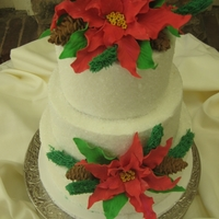 "Poinsettias For A Reduation 10"", 8"", 6"" iced in bc with crystal sugar coating applied. Poinsettias are fondant/gumpaste, pinecones are royal icing, and..."