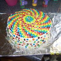 Rainbow Cake 3 eight inch layers with butter cream frosting and a big bag of M&M's. Made for a school carnival.