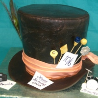 The Mad Hatters Hat 3 8x2 cakes and a 9x2 cake, stacked and trimmed, ganached and covered in fondant. Used a piece of lace to emboss fondant and airbrushed...