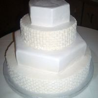 Simple Wedding Cake Fluffy white cake with pure white buttercream. Basketweave buttercream and white chocolate fondant adorne alternating tiers.