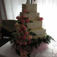 Sara's Wedding Cake 4 tier White cake, white buttercream, off-white accents with silver dragees. Fresh pink roses. This cake tipped over while placing on the...