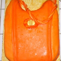 Purse Orange cake with buttercream icing and filling covered with MMF.