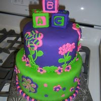Baby Girl Shower Cake Purple, Pink, and Green decorated cake. Baby Block petit four cakes on top