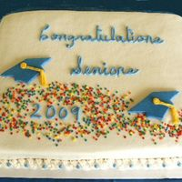 2009Gradresize.jpg All white buttercream background accented with blue and rolled buttercream graduation caps and confetti sprinkles complete this celebration...