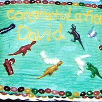 Dinosaur Cake! Buttercream covered sheet cake with dinosaur decorations and jelly beans.