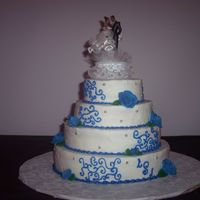 Blue And Silver Wedding This cake I did for a couple who wanted two cakes. Cake is strawberry cheesecake flavor with strawberry filling, BC icing and RI roses....