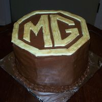 Mg   Buttercream with fondant accents. This was made for a MG car club annual party.