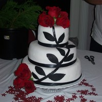 Classy Cake top and bottom layer is white cake and middle is red velvet.. all has butter cream icing and fondant. Black fondant leaves and stem . black...
