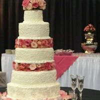Cassie's Wedding Cake All buttercream iced and decorated cake accented with fresh roses of various pink hues.