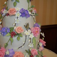 Floral Cake This cake features gumpaste and fondant peonies, roses, berries, apple blossoms and butterflies, all handmade and handpainted. The tiers...