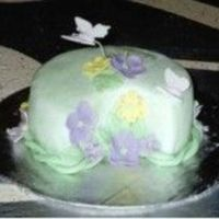 Small Green Half Moon Shaped Fondant Cake With Flowers And Butterflies.