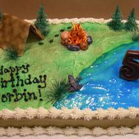 Camping Theme This is a chocolate cake with buttercream. The water is blue gel, and the tent is a pretzel frame held together with chocolate almond bark...