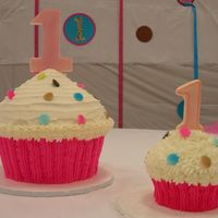 Giant And Baby Cupcake These were made from the Wilton Giant Cupcake pan and the cupcake pan with 4 medium cupcakes. All white with buttercream. Fondant dots and...