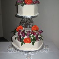 "Hexagon Wedding 15"" 12"" and 9"" hexagon cakes with top tier supported by wine glasses. Fresh flowers to decorate."