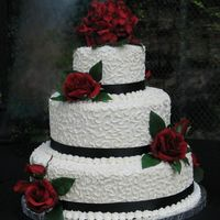 Burgundy Rose   White chocolate buttercream frosting with cornelli lace. Black ribbon and silk flowers selected by bride.