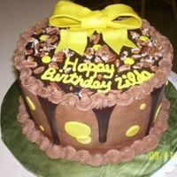 Chocolate White cake, turtle filling, yellow fondant bow w/gold luster dust.