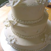 Wedding Cake - Simple Cream Color With Gumpaste Flowers A very lovely young bride I work with requested this one. Buttercream with sugarpaste flowers. Thanks for looking!