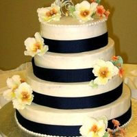 Wedding Cake - Blue With Peonies This was a buttercream cake with satin navy blue ribbon, gumpaste peonies in orange and yellow and orange primroses for coordinating design...