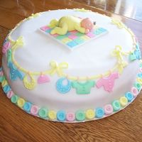 Baby Shower Cake Baby sleeping on quilt, baby clothes line top border/side decoration, button bottom border; all decorations made with fondant