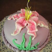 Sarah's Birthday Cake We have a staff member who loves the color purple and stargazer lilies. The covering is a combination Rolled Butter Cream and Fondant. The...