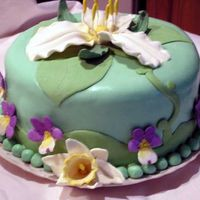 Trillium Cake Trillium, daffodils and violets are made out of modeling chocolate. Background is rolled buttercream.