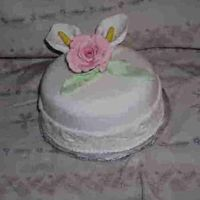 Little White Cake This mini is covered in white fondand, it has a band around of embossed roses and pink rose on top. It is chocolate cake with buttercream...