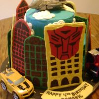 Transformers Thanks for all the ideas on here! Chocolate cake with chocchip buttercream. The buildings are made out of chocolate. Toys are real(4y/o...