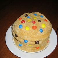 "M & M Cookie Cake The cake is a 6"" white cake with chocolate chip cookie dough filling, covered in buttercream with crushed vanilla wafers for texture...."