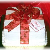 "Christmas Present Wrapped In Red Ribbon 9"" square iced in buttercream with red fabric ribbon and bow."