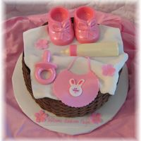 Baby Girl Items In Basket... Everything is edible. Fondant bib, blanket and flowers. Chocolate booties, bottle and pacifier. Thanks for looking! :)