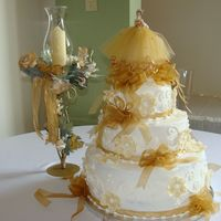 136.jpg 3 tier cake 14-10-6 with buttercream icing. The flowers were made with fondant and dusted with gold luster.
