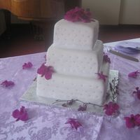 Orchid Wedding Cake fondant covered tiers, with pearl accents and sheer ribbon. Real orchids on case and around table. TFL