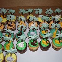 King Of The Jungle Cupcakes Cupcakes w/BC frosting. Animals and trees are candy melts molded into those shapes. The theme of the shower was king of the jungle.
