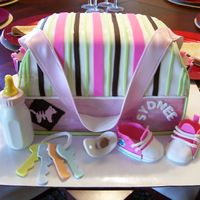 First Diaper Bag Cake White almond and yellow cake covered in fondant. Fondant shoes, keys, and pacifier. Bottle is molded of solid white chocolate