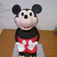 "Mickey Mouse Head made w/RKTs and covered in fondant. Body made in a Pyrex bowl and 2 7"" rounds. Mickey is sitting on a box made of cake. Arms,..."