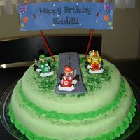 Mario Kart Birthday Cake This is a double chocolate cake covered in fondant and a buttercream border. The road is also made of fondant wth green sprinkles as grass...