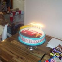 "Lightning Mcqueen Cars Cake Second shot of cake with candles. ""Happy Birthday Brandon"" was piped around the side of the cake which I had frosted with a &quot..."