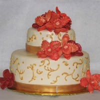 Orange Orchid Cake Champagne Colored fondant w/ Orange Orchids and Maroon Plumeria. Made for a Hawaiian Beach Wedding