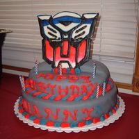Transformers this cake was for a nine year old he wanted transformers the logo is made of black and white color flow the cake is covered in almond...
