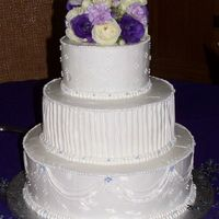 "25Th Silver Wedding Anniversary Cake 3 Tier Cake with White Buttercream icing. Purple accents. Fresh floral topper with Wilton ""25"" pick."