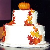 Fall Wedding Cake Two tiered fall wedding cake. Mini pumpkin topper. Fondant leaves and acorns. Carrot cake with vanilla buttercream.