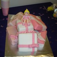 Presents For Baby chocolate cake with chocolate/coconut filling and fondant on top. gumpaste figurine on top.